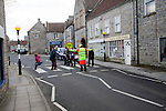Lollipop man stopping traffic to allow people to cross the road safely, Somerton, Somerset, England