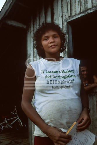 Xapuri, Acre State, Brazil. Rubber tapper woman holding a text book 'I like to read and write'  outside her wooden house wearing a t-shirt from the Fourth National Rubber Tappers' Meeting, 1995.