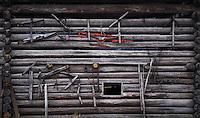 Side of an old barn with farm tools and implements hanging on it.