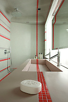 Red stripes of mosaic tiles include a dramatic strip which runs across the Corian stone wash basin and up the wall of the walk-in shower