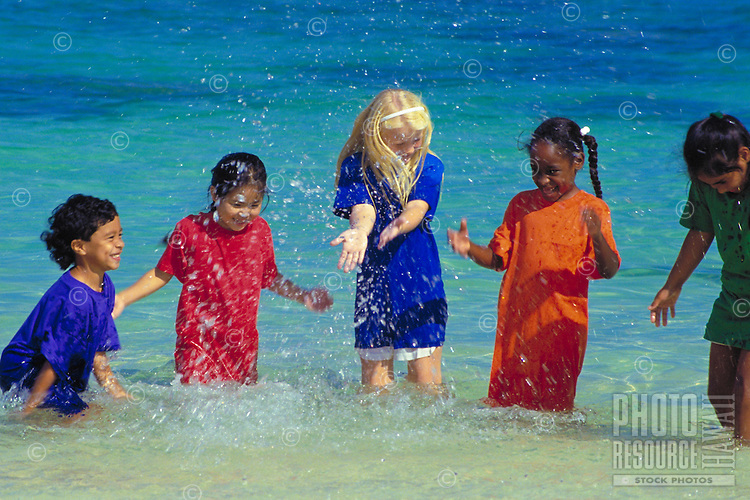 Children wearing bright colorful clothes splash water near the shore at the beach.