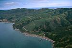 Aerial over green hills above the coast and water near Prisoners Harbor, Santa Cruz Island, Channel Islands, California