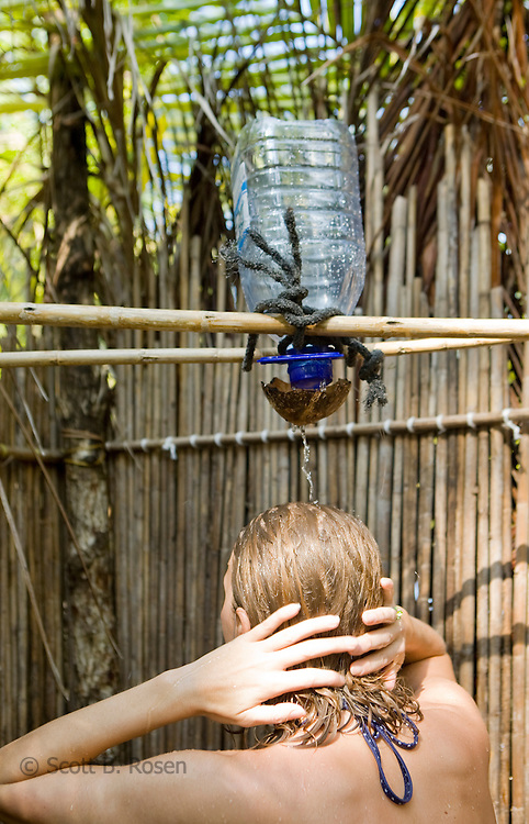 A young woman take a shower using water filtered through a coconut, on Isla Pelikano, San Blas Islands, Kuna Yala, Panama