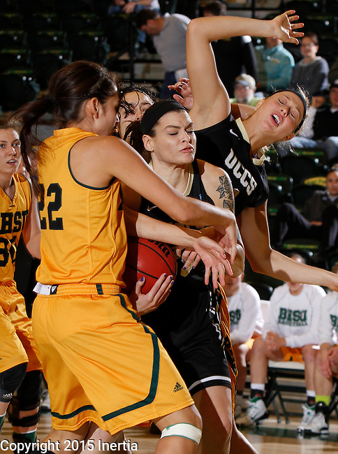 JANUARY 23, 2015 -- Chelsey Biegler #22 of Black Hills State reaches on Brittany Hernandez #35 of UC-Colorado Springs during their Rocky Mountain Athletic Conference women's basketball game Friday at the Donald E. Young Center in Spearfish, S.D.  Tori Fisher #11 of UCCS is in the background. (Photo by Dick Carlson/Inertia)