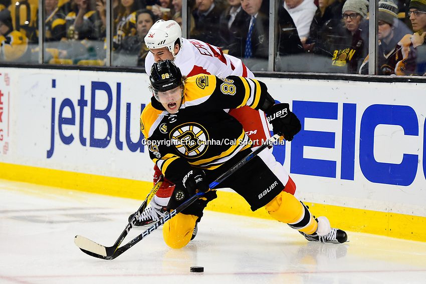Tuesday, January 24, 2017: Boston Bruins right wing David Pastrnak (88) has his stick checked by Detroit Red Wings defenseman Jonathan Ericsson (52) during the National Hockey League game between the Detroit Red Wings and the Boston Bruins held at TD Garden, in Boston, Mass. Boston defeats Detroit 4-3 in overtime. Eric Canha/CSM