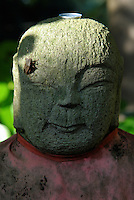 A jizo statue on Mount Takao. Pilgrims place coins on the statues as they pray.