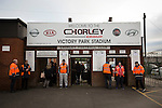 Stewards stand on duty at the entrance to Victory Park, before Chorley played Altrincham in a Vanarama National League North fixture. Chorley were founded in 1883 and moved into their present ground in 1920. The match was won by the home team by 2-0, watched by an above-average attendance of 1127.