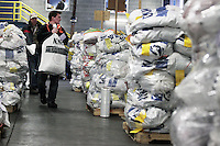 Wednesday, February 13, 2013.  Volunteer, Elder Mark Bell of the LDS church Helping Hands ministry, carries a food bag to the appropriate checkpoint stack during the musher's food drop day at Airland Transport in Anchorage..Iditarod 2013