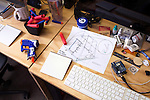 A desk at Reaction Housing with a nerf gun and 2-d design plans of Exo units.