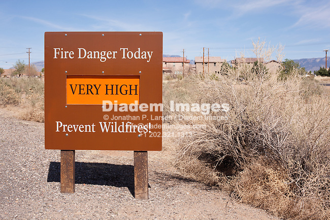 A fire danger sign and dry brush near an Albuquerque, New Mexico, neighborhood.
