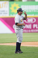 Charleston RiverDogs manager Luis Dorante (25) goes through the signs from the third base coaches box during the game against the Hickory Crawdads at L.P. Frans Stadium on May 25, 2014 in Hickory, North Carolina.  The RiverDogs defeated the Crawdads 17-10.  (Brian Westerholt/Four Seam Images)
