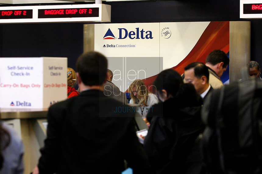 Passengers and workers at a Delta Air Lines check-in counter at Hartsfield-Jackson Atlanta International Airport. US Airways has made a bid to take over Delta Air Lines, which is headquartered in Atlanta.<br />