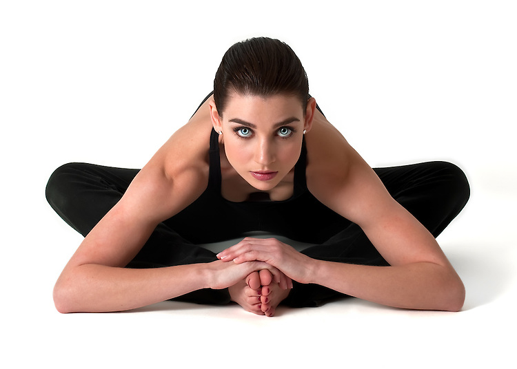 Beautiful young brunette woman in yoga pose on white background