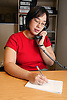 Single parent at work talking on a telephone in office,