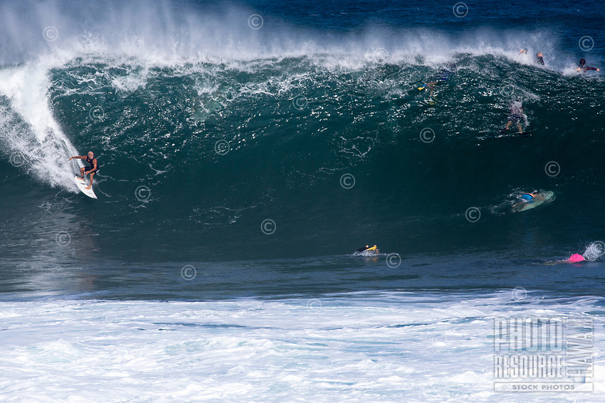 Legendary surfer Michael Ho rides a big wave while others respectfully get out of the way at Pipeline (off of 'Ehukai Beach Park), North Shore, O'ahu.