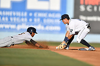 Asheville Tourists shortstop Jose Gomez (4) fields a pickoff throw and attempts to put the tag on Isiah Gilliam (25) during a game against the Charleston RiverDogs at McCormick Field on July 5, 2017 in Asheville, North Carolina. The RiverDogs defeated the Tourists 10-9. (Tony Farlow/Four Seam Images)