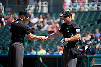 Umpires Andrew Barrett and Brian Walsh shake hands before a Texas League game between the Amarillo Sod Poodles and Frisco RoughRiders on May 19, 2019 at Dr Pepper Ballpark in Frisco, Texas.  (Mike Augustin/Four Seam Images)