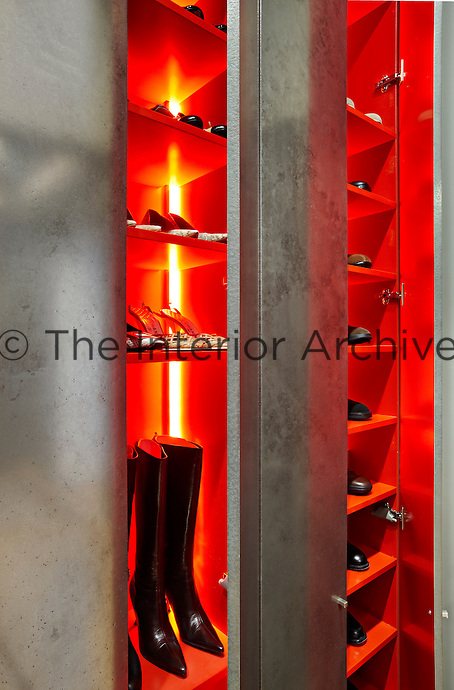 Shoes and boots are stored in a custom-made red shelving unit with built-in lighting.