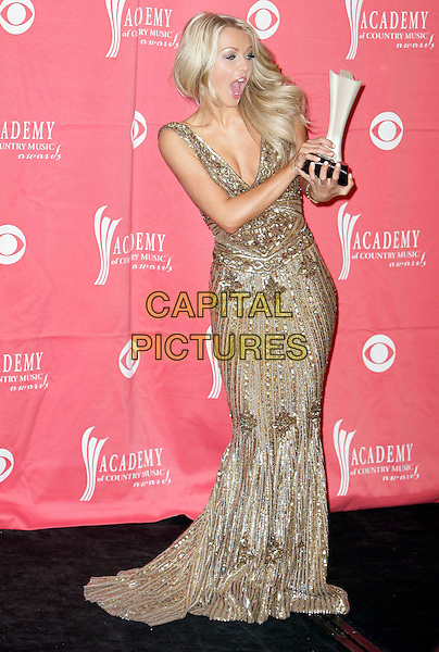JULIANNE HOUGH.Pressroom at the 44th Annual Academy Of Country Music Awards held at the MGM Grand Garden Arena, Las Vegas, Nevada, USA..April 5th, 2009.full length gold dress sequins sequined long silver award trophy mouth open funny face .CAP/ADM/MJT.© MJT/AdMedia/Capital Pictures.