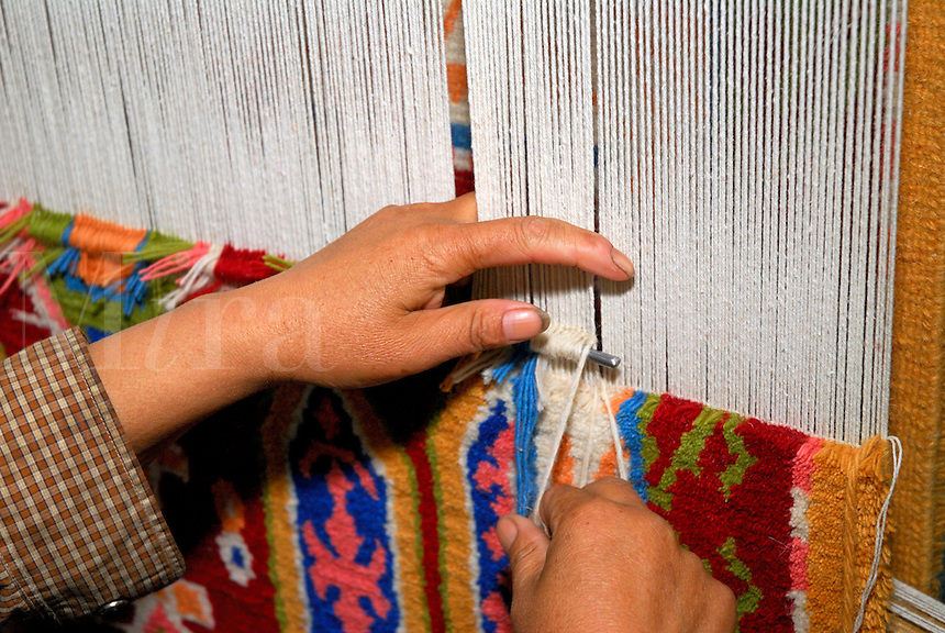 Tibetan woman hand weaving a traditional yak-wool carpet with tribal design, on a loom in a carpet factory, Lhasa, Tibet.
