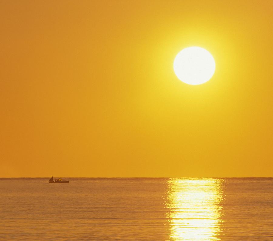 Fishing boat on ocean below rising sun off the coast of Maine, Atlantic Ocean, Maine
