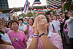 """Apr. 2, 2010 - BANGKOK, THAILAND: A pink shirt protestor covers her mouth while screaming obscenities directed to Red Shirt protestors who are disrupting life in Bangkok. Thousands of """"Pink Shirts,"""" who claim to be neither """"Red Shirts"""" nor """"Yellow Shirts"""" nicknames for Thailand's dueling political forces, gathered in Lumpini Park in central Bangkok Friday evening to call for """"peace in the land,"""" a play on the Red Shirts slogan, """"Red in the Land."""" The """"Pink Shirts"""" represented educators, business people and people in the tourist industry, all of which have been hurt by the ongoing political protests that have disrupted life in the Thai capital. The """"Pink Shirts"""" stressed their loyalty to His Majesty Bhumibol Adulyadej, the King of Thailand, and chanted for the Red Shirts to """"Get Out!"""" of Bangkok.    PHOTO BY JACK KURTZ"""