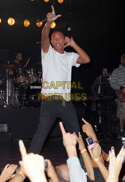 PHARRELL WILLIAMS .at Perez Hilton's 'One Night In Los Angeles' held at the Wiltern Theatre, USA, Los Angeles, CA, USA, .11th September 2010..half  length on stage music concert gig performing white t-shirt tattoos hand arm raised up black trousers listening gesture .CAP/ADM/DT.©Daniel Tanner/AdMedia/Capital Pictures.