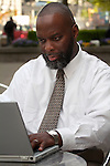African American man with laptop looking serious