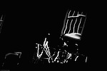 The abstract distortion and irregular shapes of a window and of bicycles parked at night.