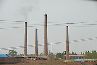 Daytime horizontal view from a train of smokestacks at a commercial manufacturing facility near Píngyáo county of the Jìnzhōng District in Shānxī Province, China  © LAN