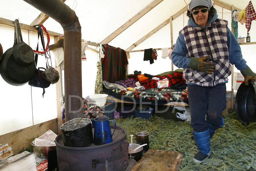 Bertha Frost walks through her cooking tent at a traditional-style winter camp near Old Crow, Yukon Territory, Canada.