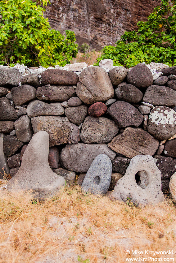 Authentic Hawaiian stone anchors along stone wall canoe shelter in Nualolo Kai village, Na Pali coast, Kauai