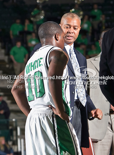 North Texas Mean Green head coach Johnny Jones talks to North Texas Mean Green guard Josh White (10) in the NCAA  basketball game between the Florida International University Panthers and the University of North Texas Mean Green at the North Texas Coliseum,the Super Pit, in Denton, Texas. UNT defeated FIU 87 to 77