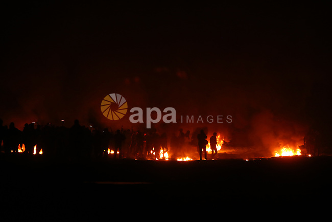 "Palestinian protesters calling themselves the ""night confusion units"" burn tires as they gather near the Gaza-Israel border east of Jabalia in the northern Gaza Strip, February 11, 2019. In northern Gaza, a so-called ""confusion unit"" also clashed with Israeli troops along the security fence, after approximately two months without such nighttime skirmishes. Photo by Dawoud Abo Alkas"