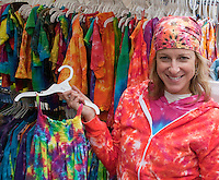 Woman holding up handmade tie-dyed garments at her Uneek sidewalk booth. Grand Old Day Festival. St Paul Minnesota MN USA
