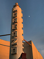 The first quarter moon floats next to the art deco structure over the entrance to the Lorenzo Theater, a vacant relic and neighborhood landmark.