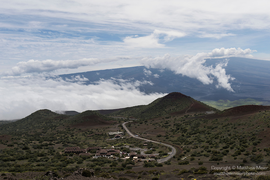 Mauna Kea, Big Island of Hawaii, Hawaii; looking down at the visitors center, above the clouds, on the drive up to the summit of the Mauna Kea Observatories (MKO), currently there are 13 independent multi-national astronomical research facilities located on the summit. Mauna Kea's altitude and isolation in the middle of the Pacific ocean make it an ideal location for astronomical observation.