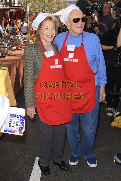 ANNE DOUGLAS & KIRK DOUGLAS.LA Mission & Anne Douglas Center's Thanksgiving Meal For The Homeless held at the Los Angeles Mission, Los Angeles, California, USA, .25 November 2009..Celebs celebrities doing charity work .full length jeans grey gray trousers green khaki jacket  married couple husband wife red apron blue jumper top sweater chef's hat .CAP/ADM/KB.©Kevan Brooks/Admedia/Capital Pictures