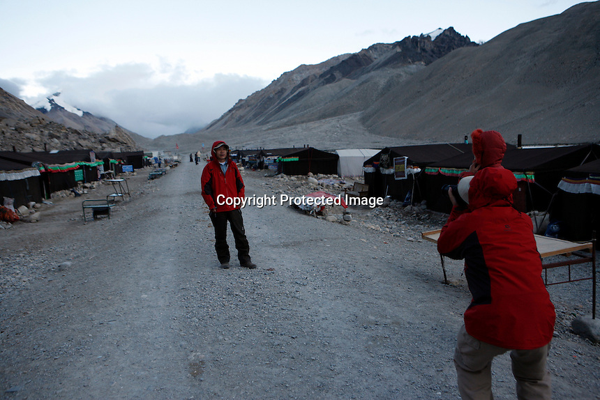 China started building a controversial 67-mile &quot;paved highway fenced with undulating guardrails&quot; to Mount Qomolangma, known in the west as Mount Everest, to help facilitate next year's Olympic Games torch relay./// Chinese tourists take photographs at the tent village near Everest base camp.<br /> Tibet, China<br /> July, 2007