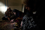 Fatma Harbeliya, right, pours tea for a visitor in her tent at Azaz Camp, just inside the Syrian border with Turkey, Feb. 24, 2013. Fatma, her mother, children and siblings have been in the camp for the past eight months. According to administrators, this camp holds roughly 9,000 to 10,000 internally displaced persons (IDP's). Two meals per day are provided by a Turkish humanitarian organization, and Qatar Red Crescent provided tents. There is very little electricity, and no running water. There is also a refugee camp on the Turkish side of the border, but it is full. The UN Refugee Agency has reported a sharp increase in refugees fleeing Syria for neighboring countries in the first months of 2013.