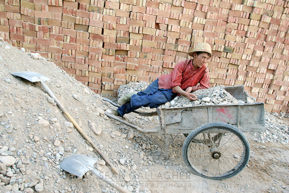 A worker takes a rest from working. Developments are putting added demands on already pressured lands. Desertification is the process by which fertile land becomes desert, typically as a result of drought, deforestation, or inappropriate agriculture. Dunhuang, Gansu Province. China