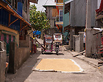 A Sampaloc standoff ensues when my tricycle meets another going the opposite direction; both of us blocked by a tarp of rice laid out on the road to dry.  (In one of the few side streets in Sampaloc, Quezon Province, the Philippines.)