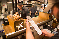 Sous chef Chris Drown (left) and Executive Chef Hart Lowry check order tickets at the expediter station in the kitchen at Hojoko, a Japanese bar and restaurant in The Verb Hotel in the Fenway neighborhood of Boston, Massachusetts, USA, on Friday, Dec. 4, 2015. The restaurant serves food as it is ready, rather than all at once; chefs check off dishes as they are completed and handed off to waiters.