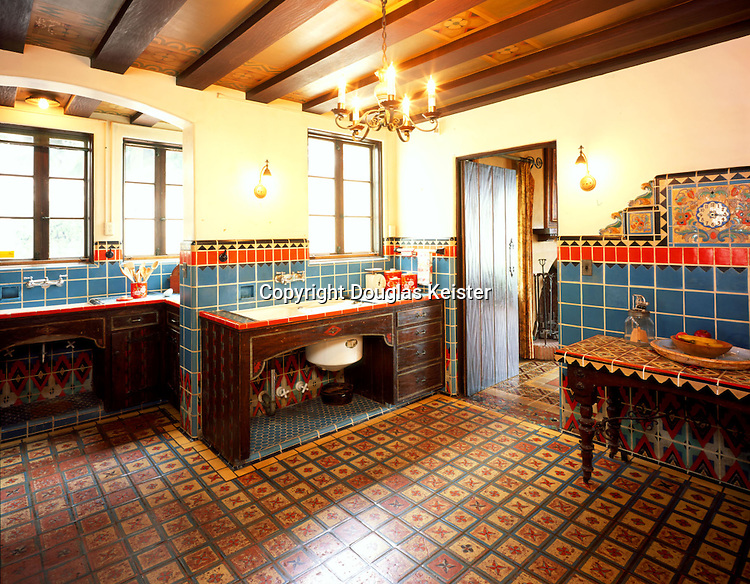 A spectacular array of Malibu tile forms the keynote in the Adamson kitchen.  The wainscot with its vivid color combination and stark geometric design departs from the more traditional Spanish motifs seen elsewhere in the house, hinting at Native American or possibly Art Deco motifs, whose popularity was just then on the ascendancy.  The device visible beneath the cabinet at center is an early dishwasher original to the house.  At left, an electric clock set in a tiled surround surmounts the wainscot; the work table beneath it features a top inlaid with Saracenic tile.  The panels between the room's ceiling beams are once again enriched with stencil-painted ornament, a favorite decorative technique of the 1920s.