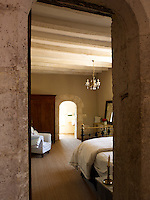 Views of an antique bed through an archway in one of the bedrooms
