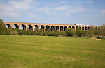Train crossing railway viaduct over the Colne valley opened in 1849, Chappel, Essex, England