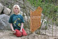 Kind, Junge hat ein Wildbienennest oder Hummelnest im Garten entdeckt und schützt es mit einem Schild und einem kleinem Weidenzaun, Wildbienennest im Garten schützen, Naturgarten