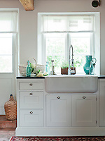 A substantial butler's sink has been set into the traditionally styled kitchen units beneath one of the windows in the kitchen