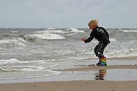 Junge spielt am Meer begeistert mit der Brandung, Strand, Lebensfreude