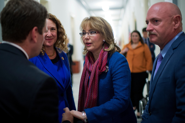 UNITED STATES - MARCH 04: Former Rep. Gabrielle Giffords, D-Ariz., greets Rep. Bob Dold, R-Ill., as Elizabeth Esty, D-Conn., and Giffords' husband Mark Kellyl, look on, before a news conference in Cannon Building to introduce legislation that would expand background checks on firearms, March 4, 2015. The bill would expand existing requirements on sales that include transactions that transpire through the internet, gun shows, and classified ads. (Photo By Tom Williams/CQ Roll Call)